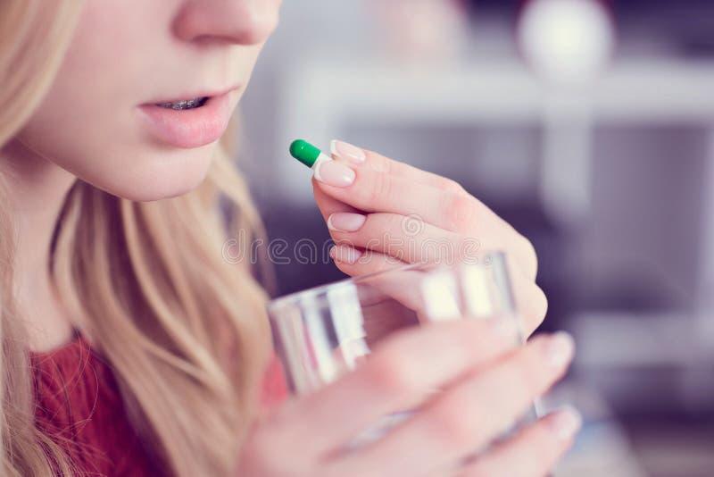 在家采取与一杯的逗人喜爱的年轻金发碧眼的女人一个药片水 免版税库存图片