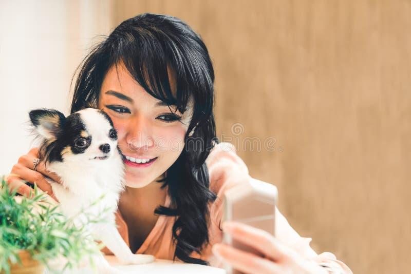 在家采取与逗人喜爱的奇瓦瓦狗狗的美丽的亚裔妇女selfie,与拷贝空间 可爱的人和宠物友谊 库存照片