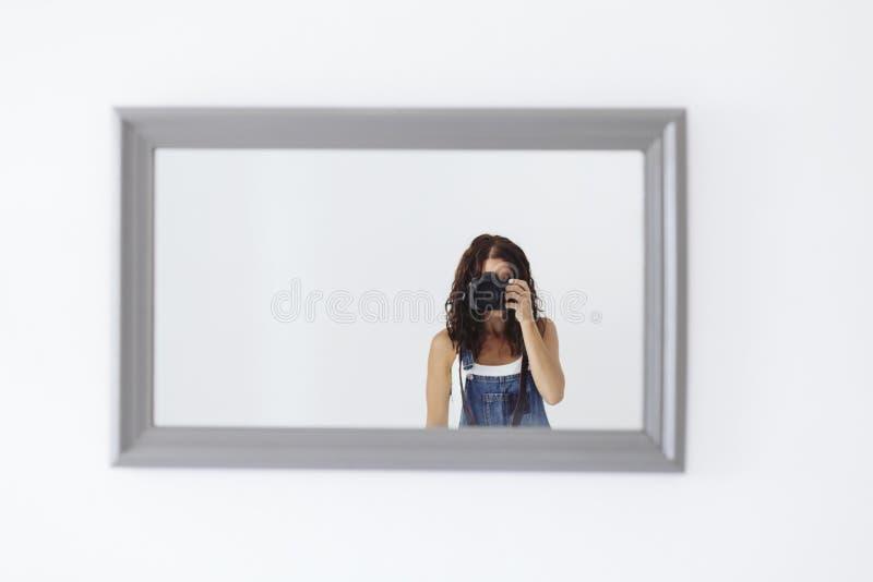 在家采取在镜子的年轻女人一张自画象 白色墙壁和背景 盖她的面孔的反光照相机 E 库存图片