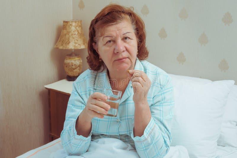 在家采取药片的资深妇女 免版税库存照片