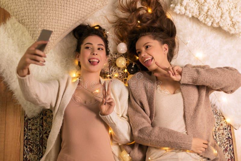 在家采取selfie的女性朋友由智能手机 免版税库存图片