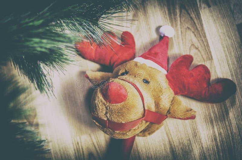 在家黏附长毛绒接近圣诞树的驯鹿玩具 免版税图库摄影