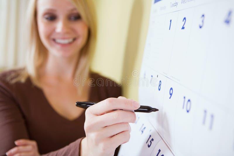 在家:准备好的妇女写计划在日历 免版税库存图片