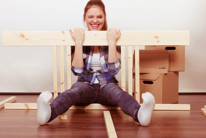 在家移动汇编家具的愉快的妇女 免版税库存照片