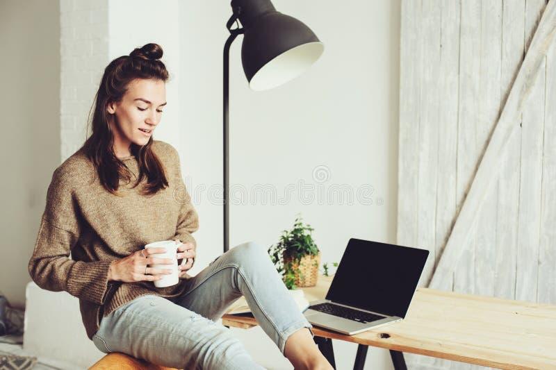 在家购物在网上与膝上型计算机和咖啡的年轻美丽的妇女早晨 免版税图库摄影