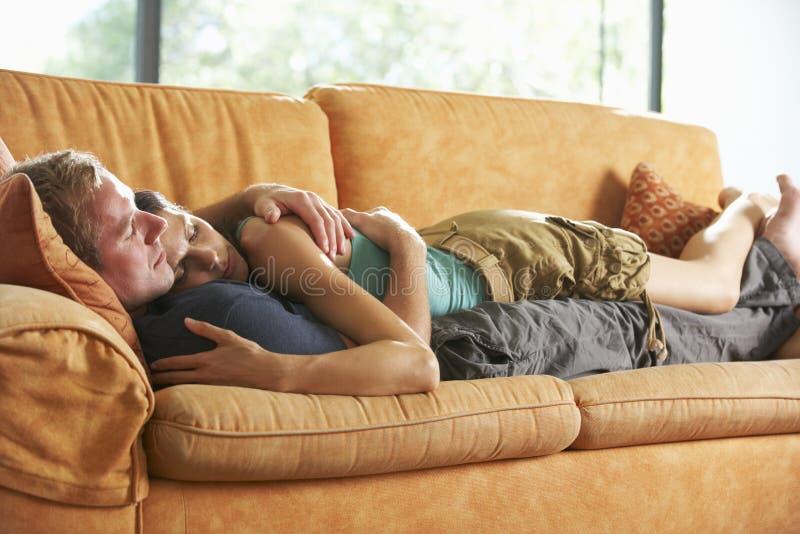 在家说谎在沙发的浪漫夫妇 图库摄影