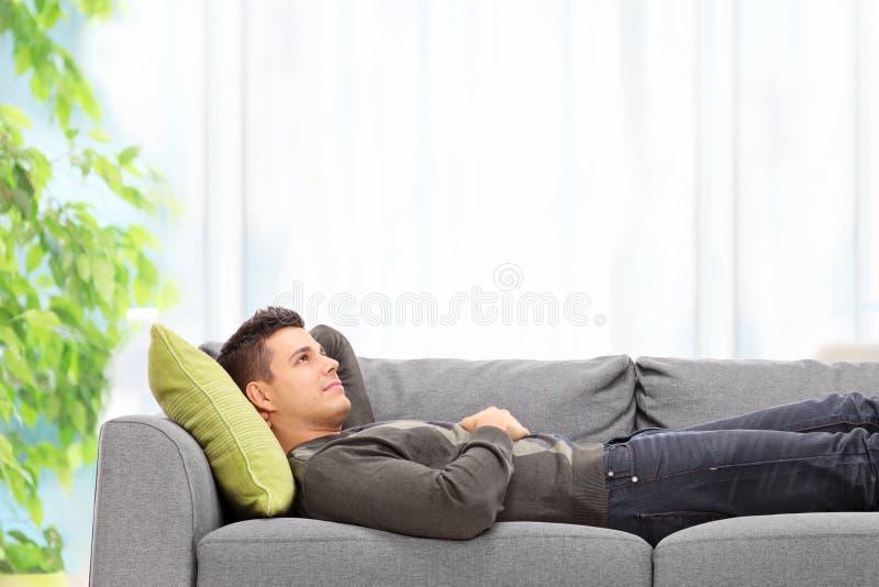 在家说谎在沙发的年轻人 图库摄影