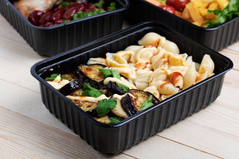 在容器的油煎的茄子有烤鸡翅和未加工的蔬菜的在土气背景、西红柿和微greenss 库存图片