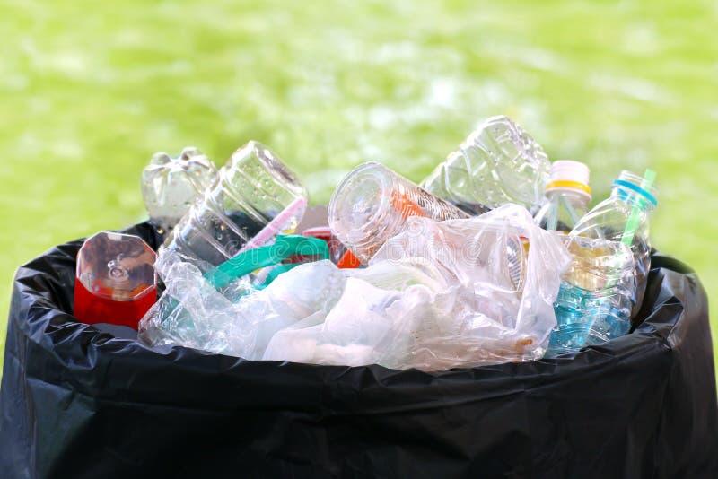在容器,废垃圾垃圾的废堆塑料塑料充分垃圾桶,塑料袋废物许多在bokeh的破烂物绿化背景 免版税库存照片