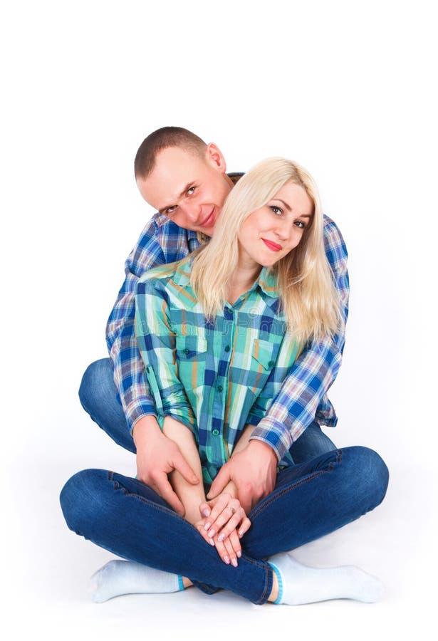在容忍的年轻夫妇坐地板在演播室 免版税库存照片