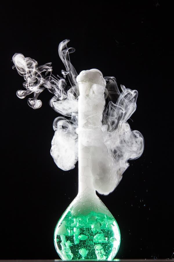 在容量瓶玻璃的化学反应在labolatory 免版税图库摄影