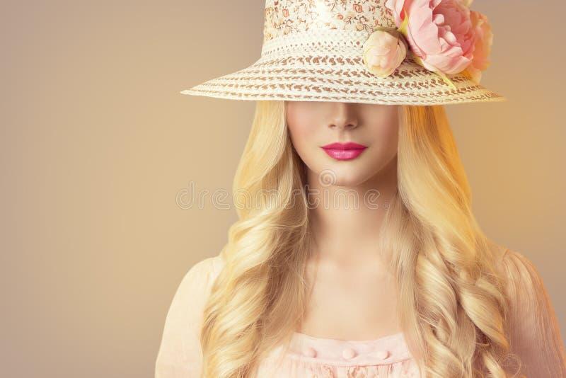 在宽广的边缘帽子有牡丹花的,减速火箭的妇女的时装模特儿 免版税库存图片