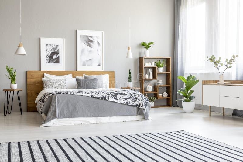 在宽敞明亮的卧室内部的镶边地毯与海报 免版税图库摄影