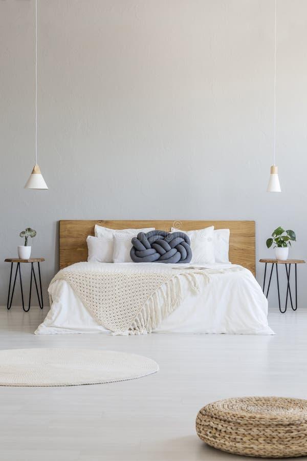在宽敞灰色卧室内部的蒲团与在床上的灯与 库存图片