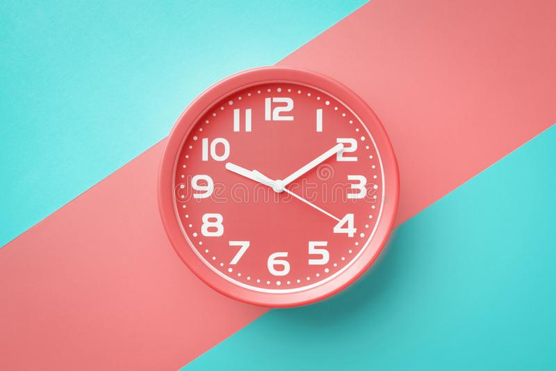 在宽红色条纹划分的对角地色的背景的顶视图圆的红色时钟 库存照片