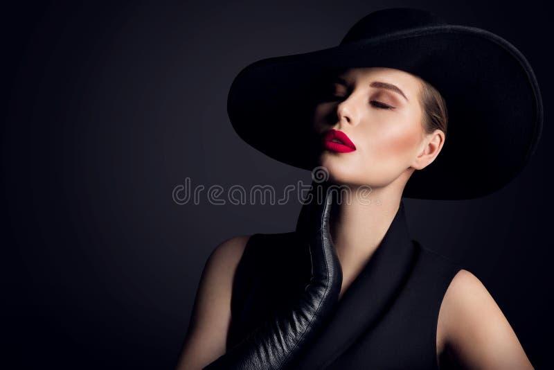在宽边缘帽子,在黑色的典雅的时装模特儿减速火箭的画象的妇女秀丽 免版税库存照片