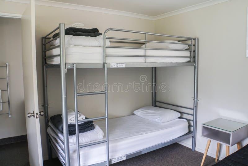在宿舍的白色简单的床 免版税库存图片