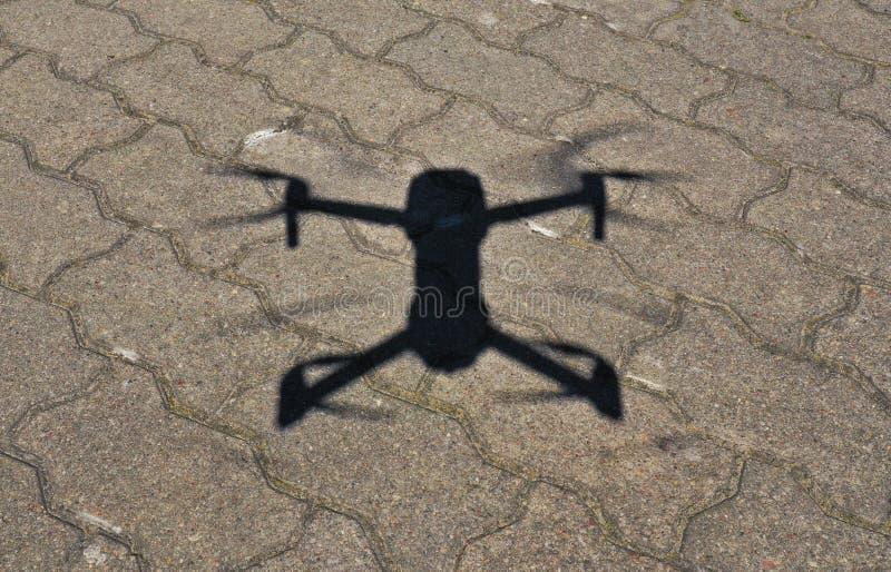 在寄生虫阴影的鸟瞰图在具体地面,在着陆程序期间的Quadcopter在好日子 免版税库存图片