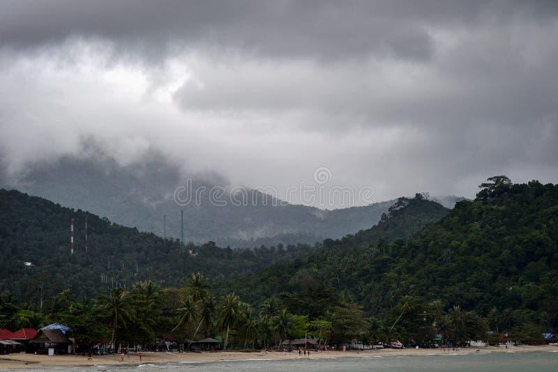 在密林的黑暗的云彩在一个小泰国村庄附近的海湾的 免版税库存图片