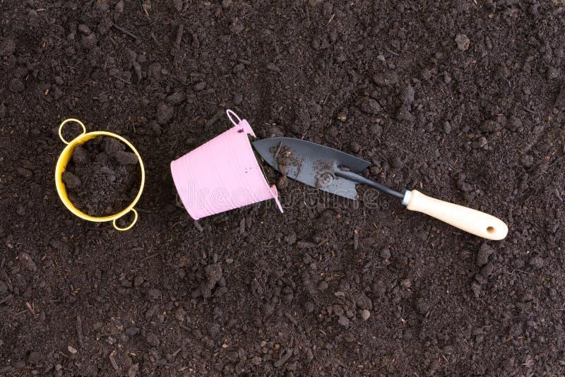 在富有的黑土壤的小桃红色和黄色桶 免版税库存图片