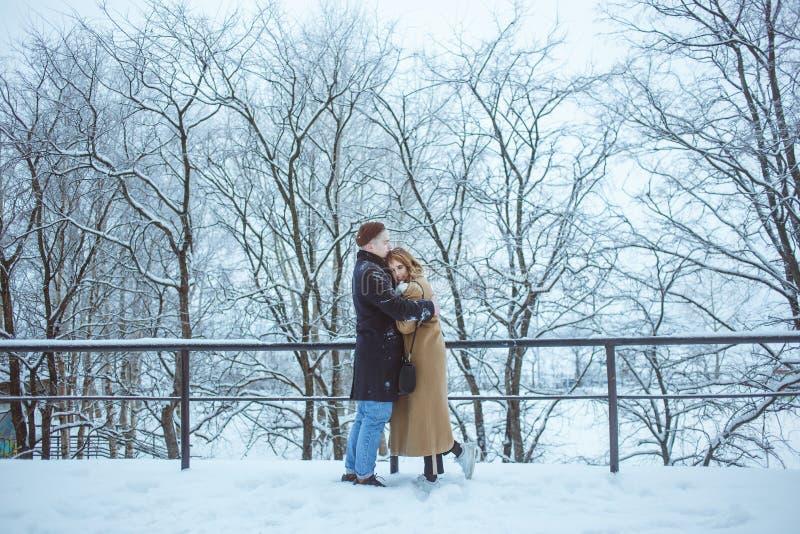 在寒假假期时结合一起拥抱外面在雪公园 古典冬天衣裳的年轻恋人 免版税库存照片