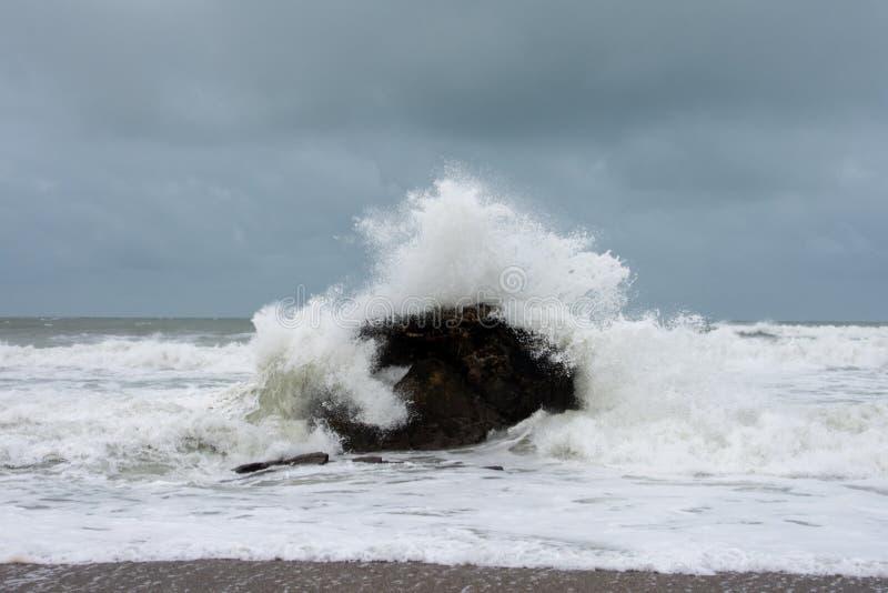 在寒冷的冬天,浪花飞溅在岩石上 图库摄影
