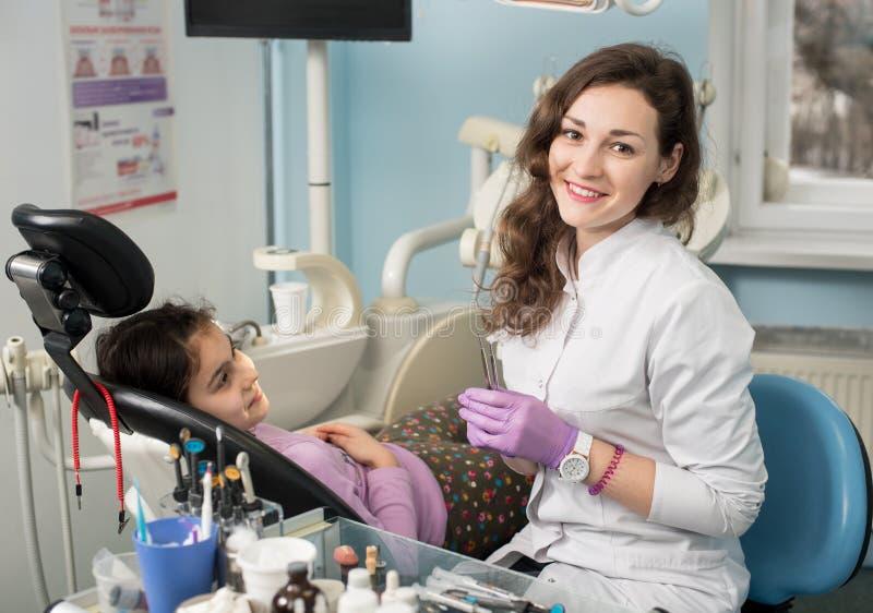 在对待牙以后的女性牙医和女孩患者在牙齿诊所办公室 免版税库存照片