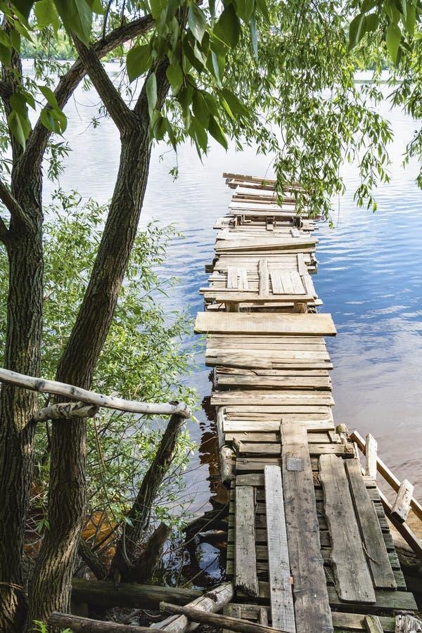 在对桥梁的老木台阶下在水 孑然的安静的干净的地方 免版税库存照片