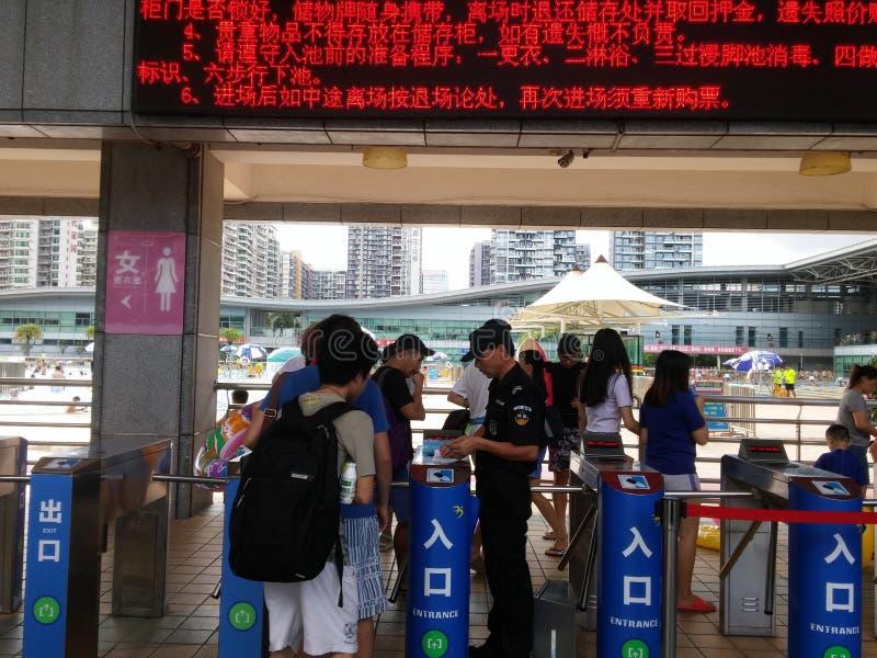 在对游泳池的入口,治安警卫检查游泳票 库存照片