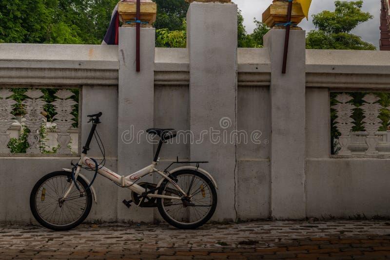 在寺庙墙壁旁边的边路停放的白色自行车 库存图片