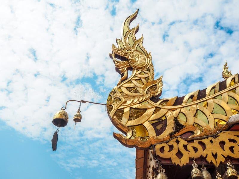 在寺庙屋顶的金黄纳卡人雕象有天空蔚蓝背景 库存图片