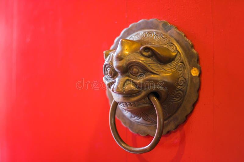 在寺庙的红色门的黄铜通道门环 免版税库存图片