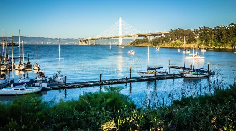 在导致奥克兰calif的新的奥克兰海湾桥梁附近的小船小游艇船坞 库存图片