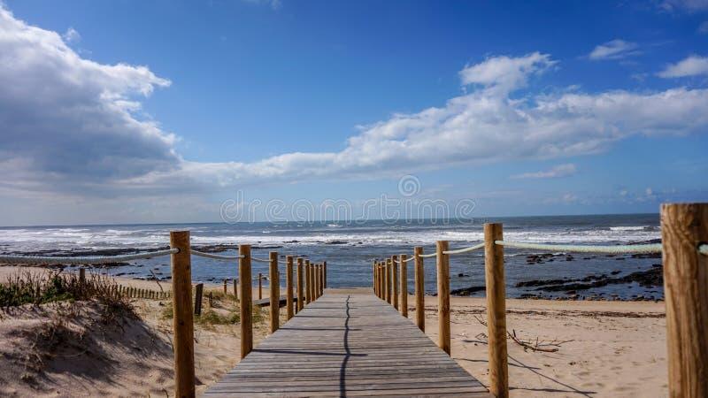 在导致海的沙丘的木板走道在一个美好和松弛海滩早晨在盖亚,波尔图,葡萄牙 免版税库存图片
