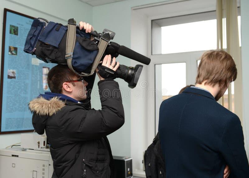 在射击期间,摄影师拿着在他的头的一台摄象机 库存照片