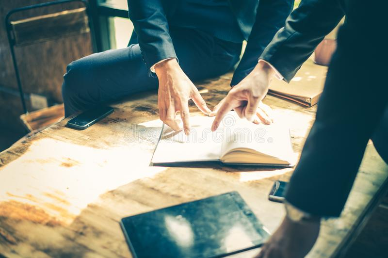 在将来销售的商人见面关于经营计划和 他们在笔记本看和点手指详述 免版税图库摄影