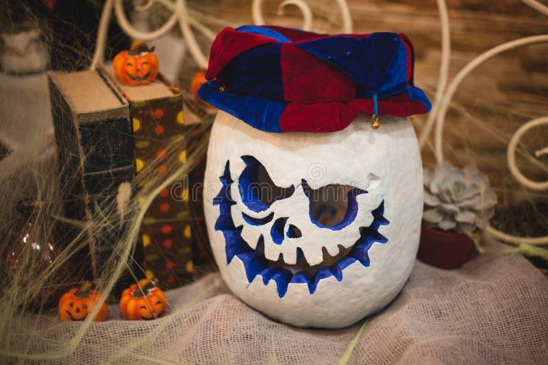 在小丑帽子的白色万圣夜南瓜头有灼烧的蜡烛的 免版税库存图片