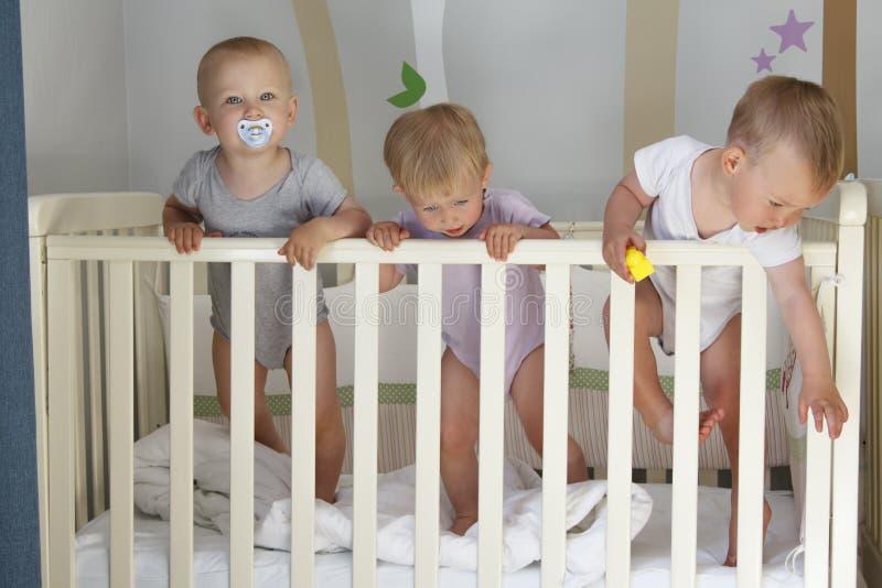 在小儿床、三胞胎婴孩两男孩和女孩的三胞胎-一起 免版税库存图片