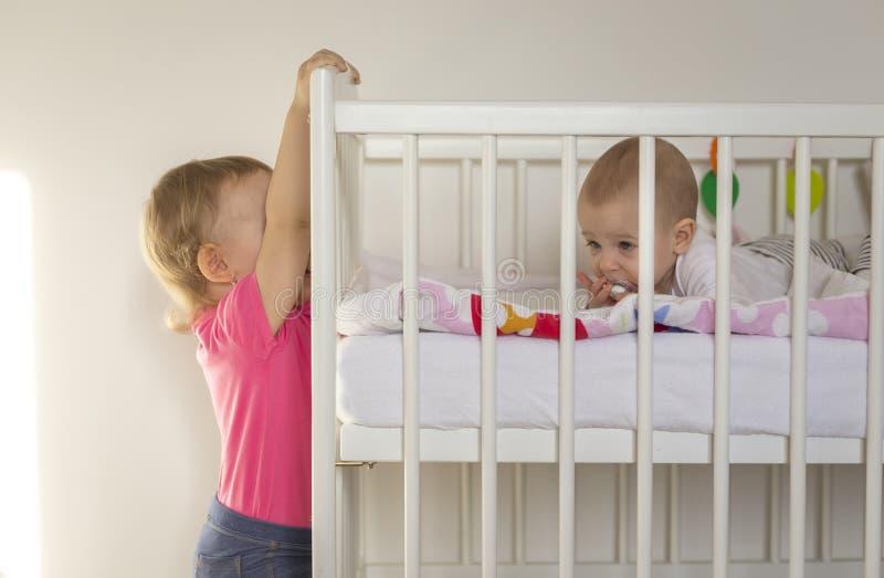 在小儿床垂悬的更老的姐妹 免版税库存照片