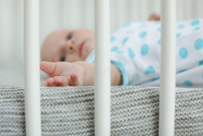 在小儿床的逗人喜爱的矮小的婴孩 库存图片