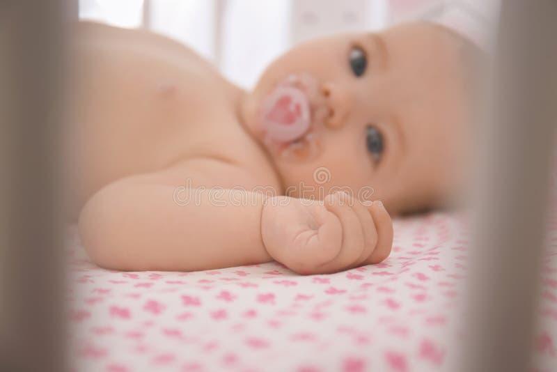 在小儿床的逗人喜爱的矮小的婴孩 图库摄影
