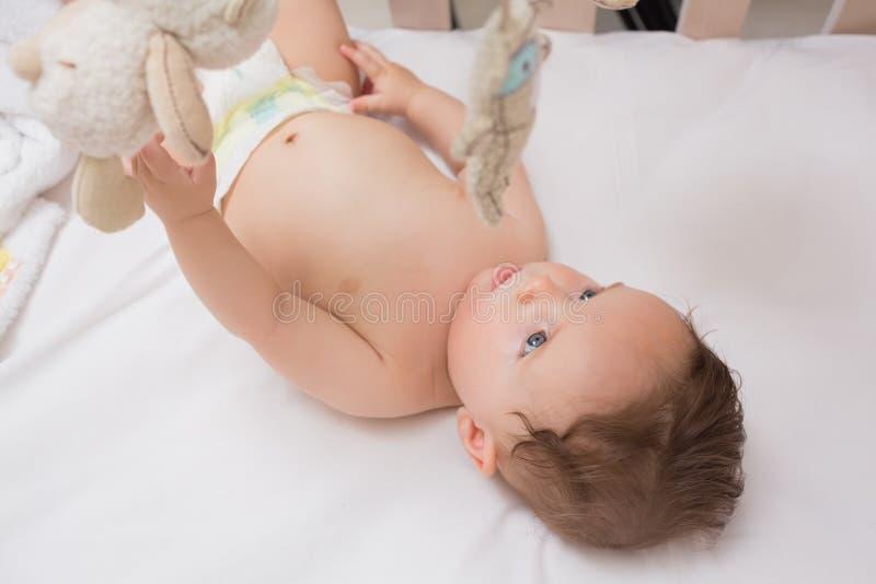 在小儿床的逗人喜爱的婴孩 图库摄影