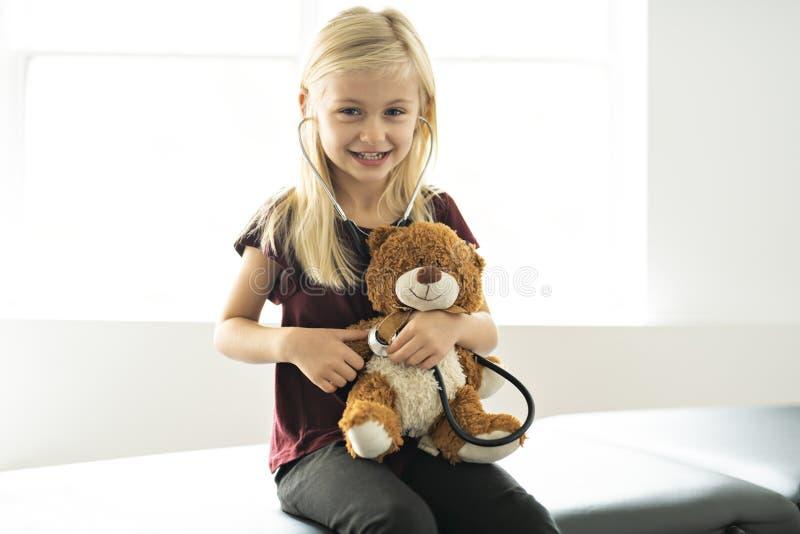 在小儿科的一头医生女孩使用和治疗熊 免版税库存照片