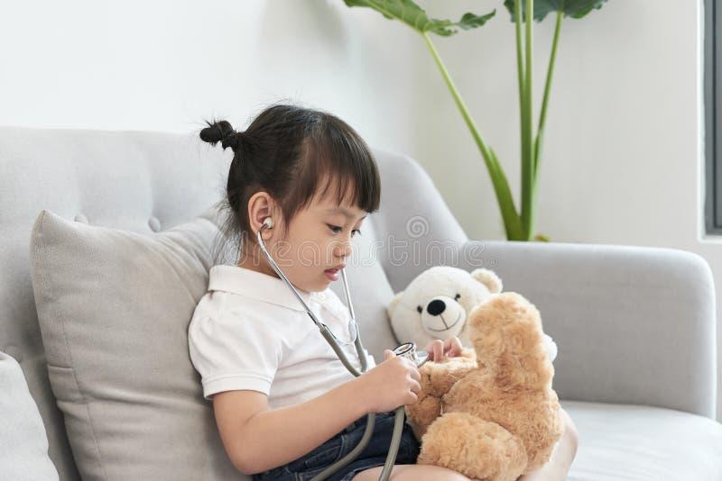 在小儿科的一头医生女孩使用和治疗熊 库存图片