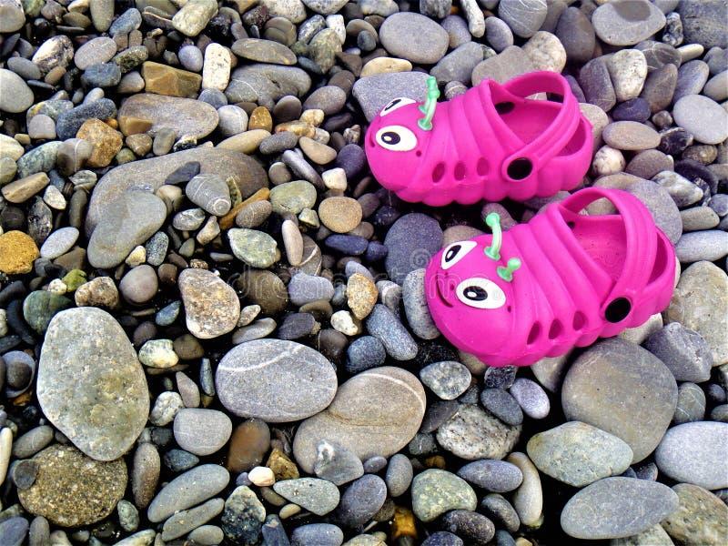 在小卵石的儿童` s橡胶拖鞋 库存图片