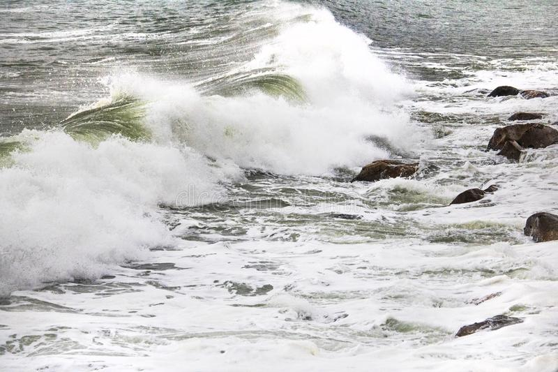 在小卵石的滚动的碰撞的波浪在克拉伦斯的一个海滩驾驶,在Kleinmond和Gordons海湾之间,西开普省,南非 免版税库存照片