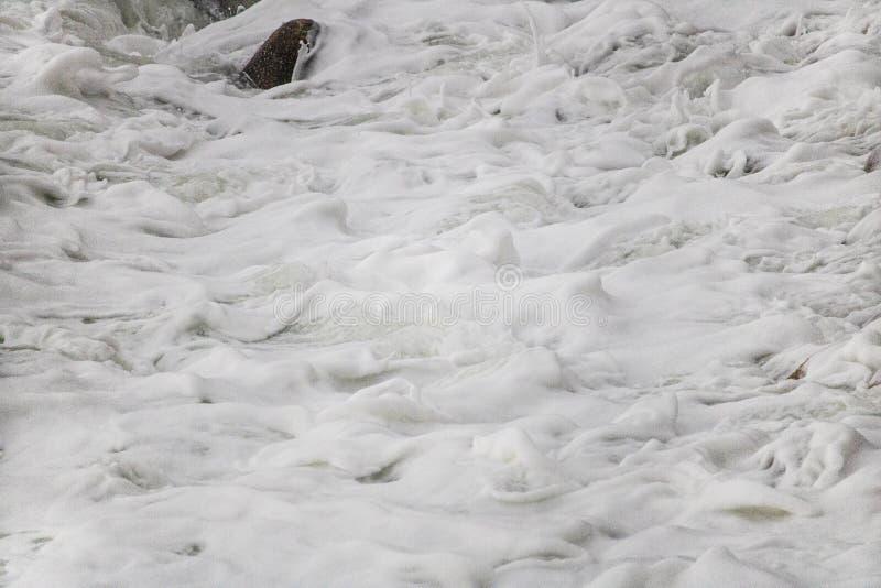 在小卵石的滚动的碰撞的波浪在克拉伦斯的一个海滩驾驶,在Kleinmond和Gordons海湾之间,西开普省,南非 免版税库存图片