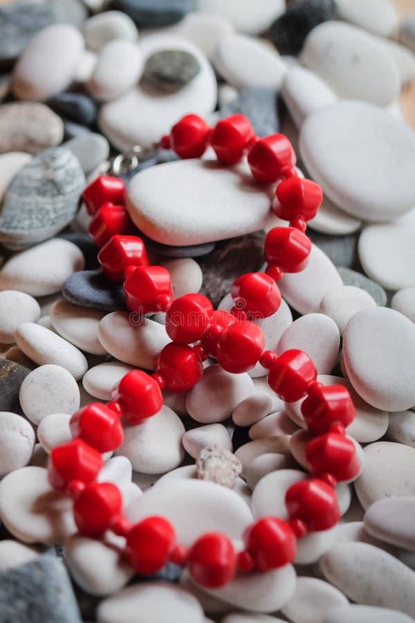 在小卵石的红色小珠 免版税库存图片
