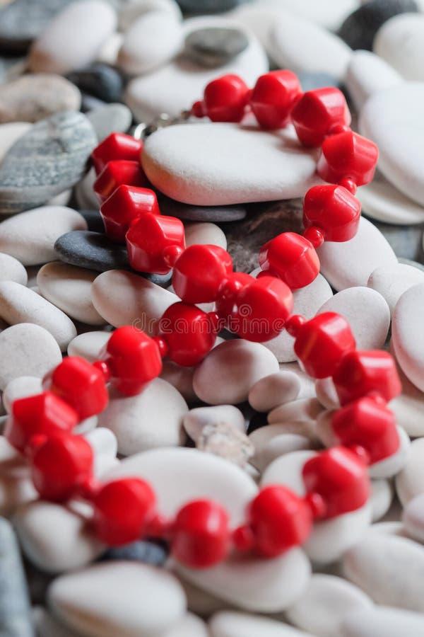 在小卵石的红色小珠 免版税库存照片