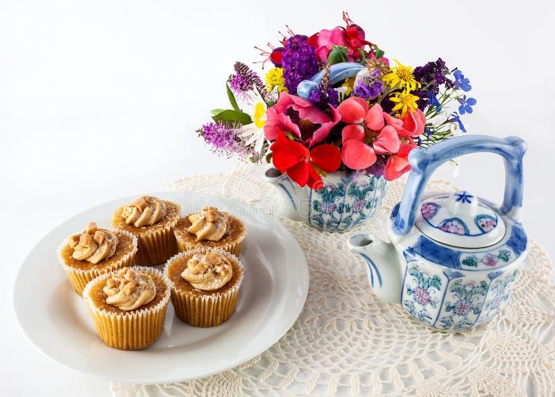在小垫布的杯形蛋糕与花 库存图片
